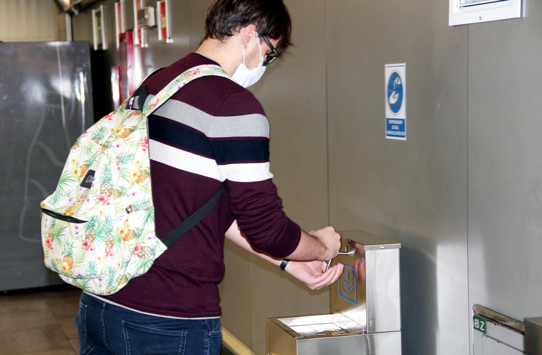 Un viajero utiliza el dispensador de hidrogel para desinfectarse las manos en la estación