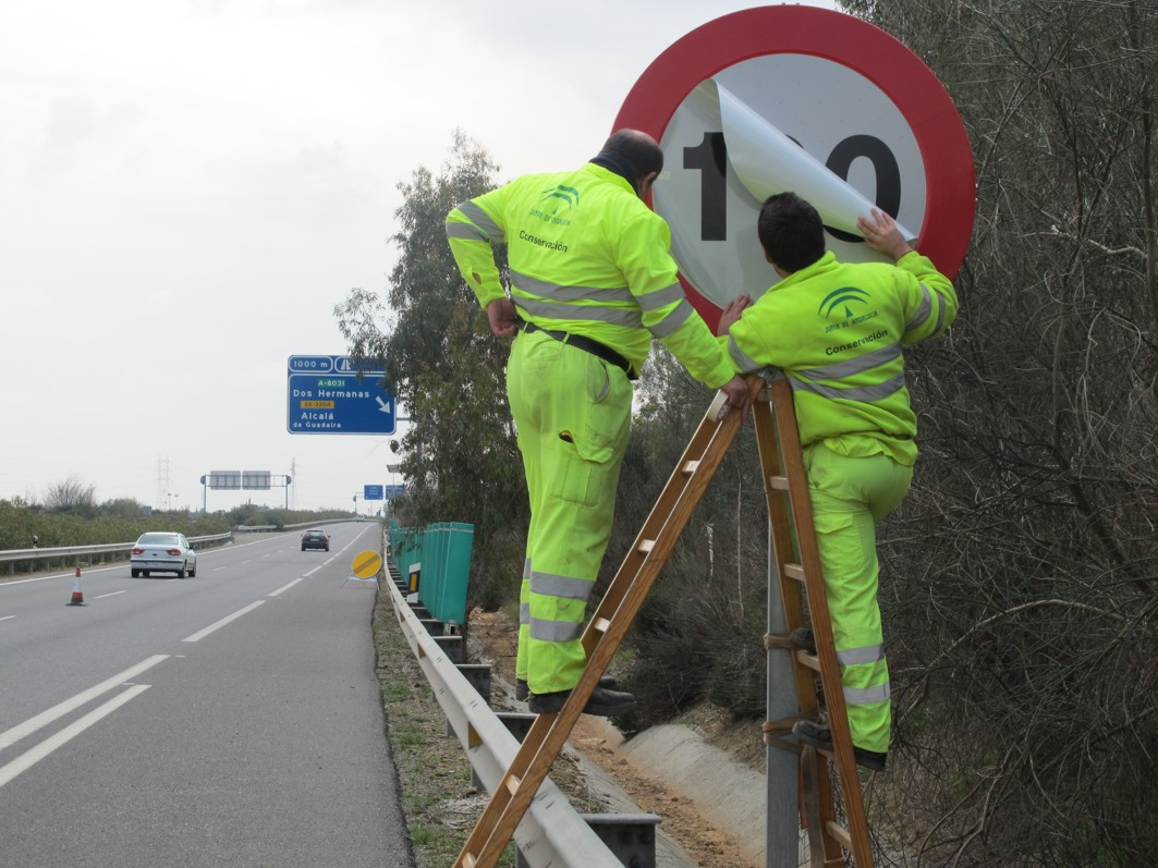 Operarios de los servicios de conservación cambian la información de la señal de límite de velocidad en la A-376 Sevilla - Utrera.